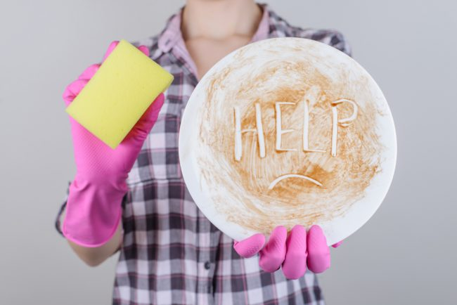 "A woman holds a dirty plate that says ""help"" while holding a yellow sponge in the other hand."