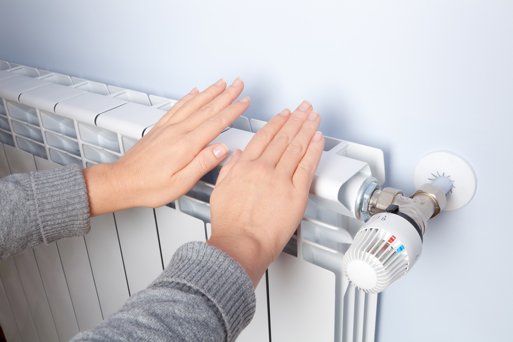 a person's hands next to a heater