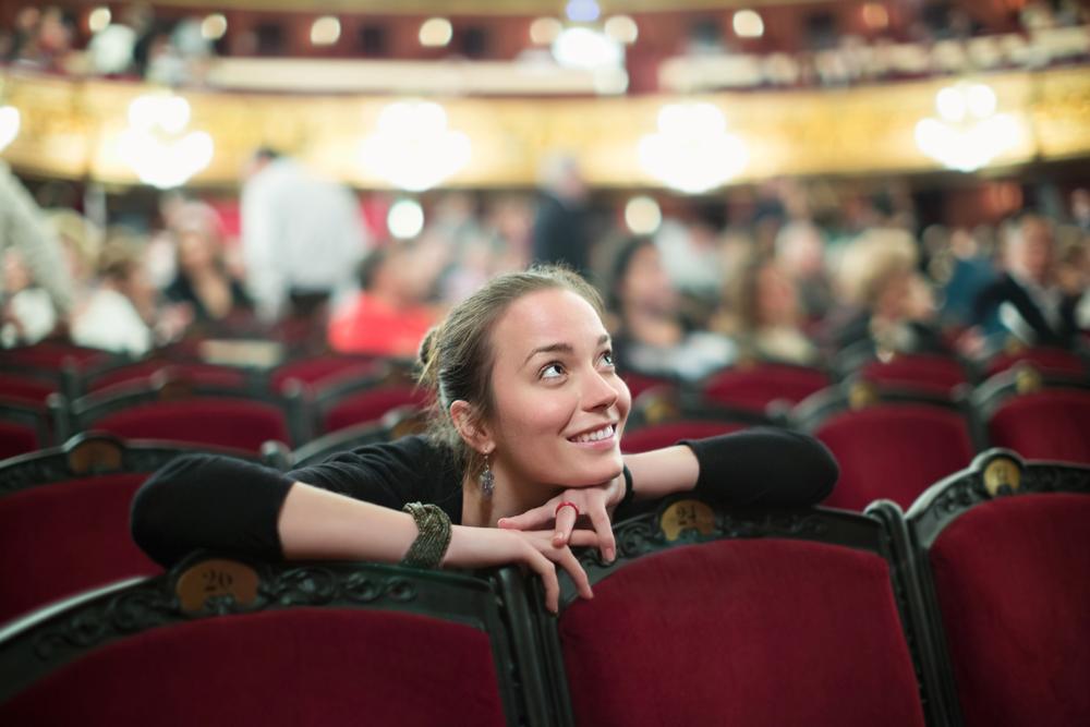 A woman gazes upward in an opera theater.