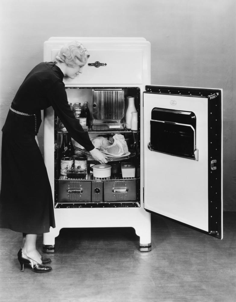 Black and white photo of a woman possibly in the 1950's pulling food out of an old refrigerator.