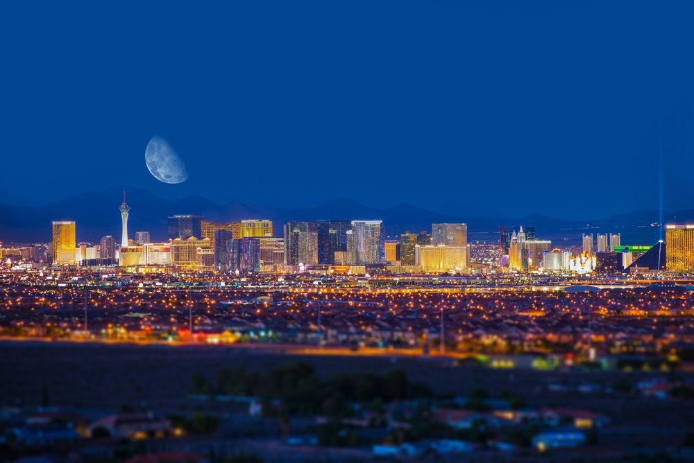 The Las Vegas skyline at night from miles away with a waning moon in the sky.