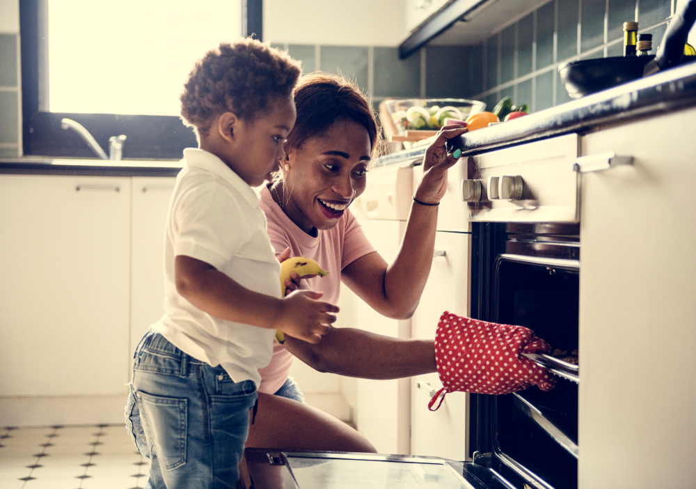 Mother and son look into oven as they remove a dish with a oven mitten.
