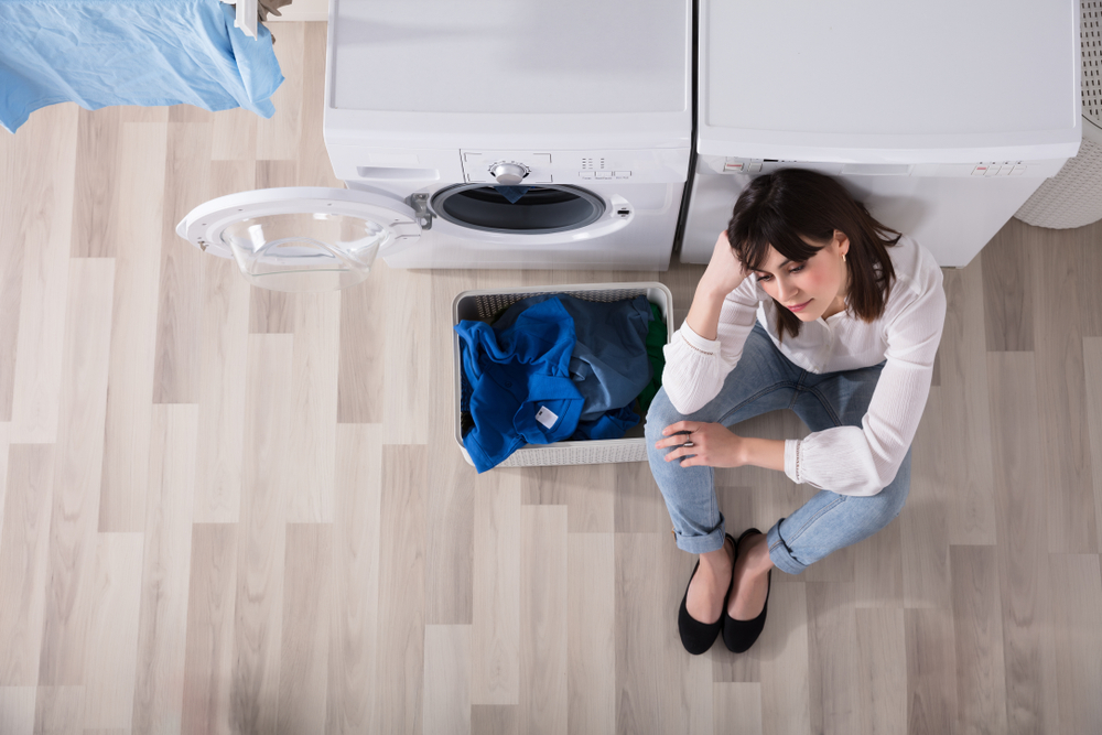 High view of a woman sitting next to a broken dryer with dirty clothes.