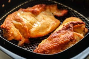 chicken cooking in an air fryer