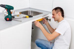 plumber fixing kitchen sink