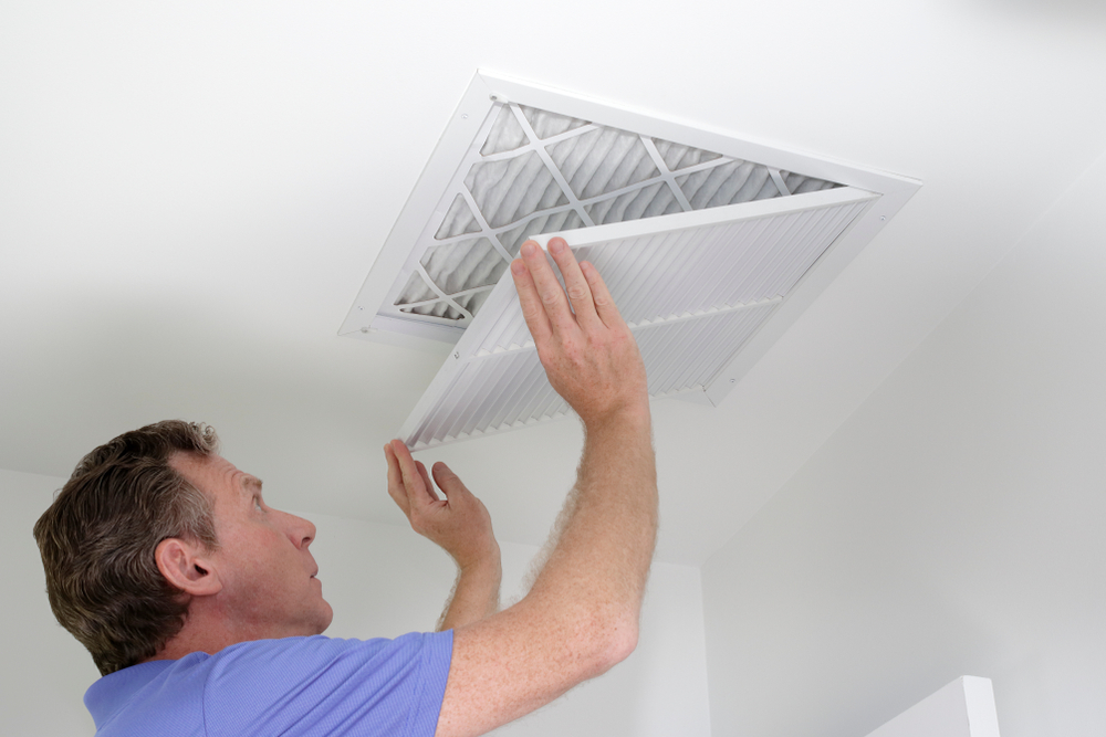 man checking on heating vent
