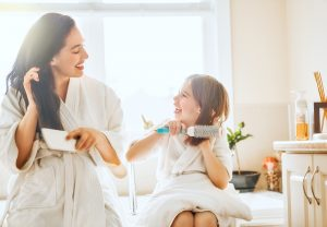 mother and daughter in bathroom brushing hair